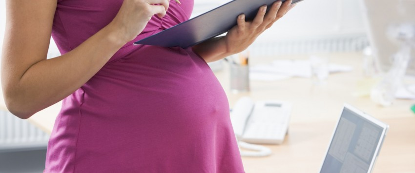 Pregnant woman at work writing in binder